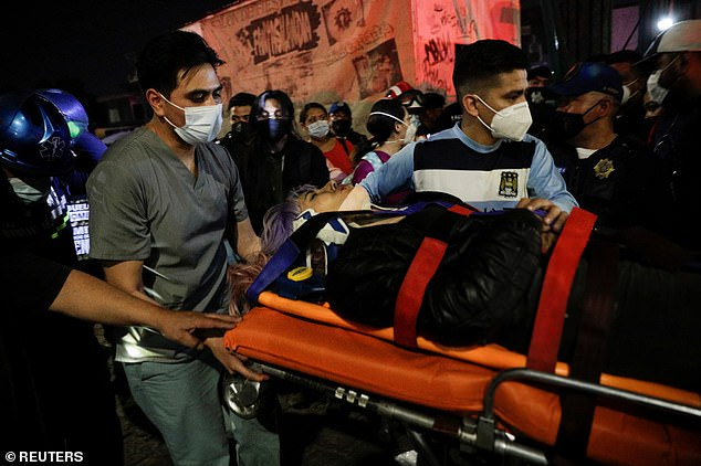 Rescuers transport an injured person on a stretcher near Olivos station in southeast Mexico City
