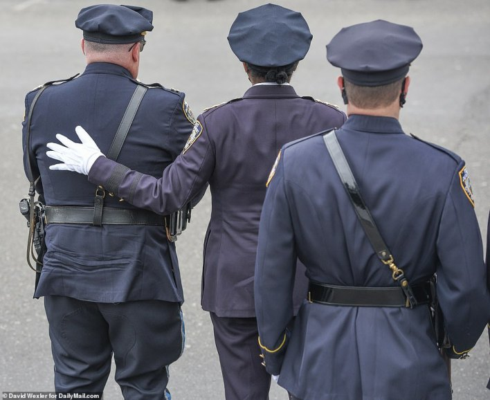 Cops comfort each other as they say goodbye to one of their own who died last Tuesday during a hit-and-run