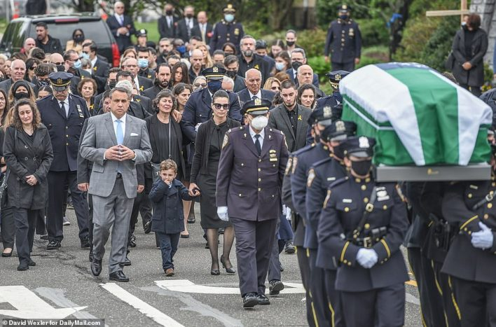 His family follow behind the pall bearers as they carry his casket out of the church following the funeral service