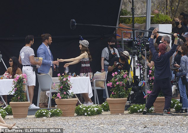 On location: Dozens of crew members could be seen to the side of the table filming the scene