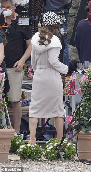 Wrapped up: Lily could be seen wearing heels as she negotiated the sandy terrain