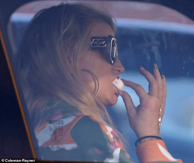 Yum: She was seen biting into a mini donuts while in the car.The Public Affair hitmaker had on a green orange and white hoodie with two diamond necklaces and large hoop earrings