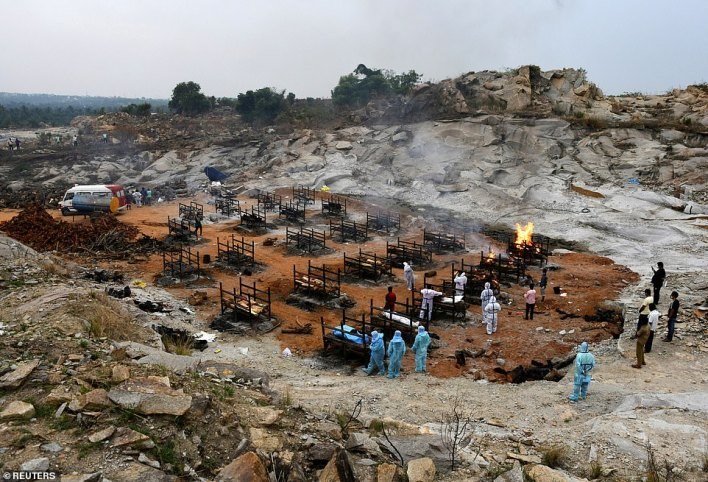 Volunteers and relatives prepare to cremate the bodies of people who died due to the coronavirus disease at a crematorium ground in Giddenahalli village on the outskirts of Bengaluru, India