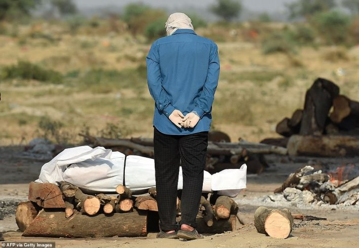 A relative mourns next to the body of his loved one who died due to the Covid-19 coronavirus at a cremation ground in Allahabad on May 4, 2021