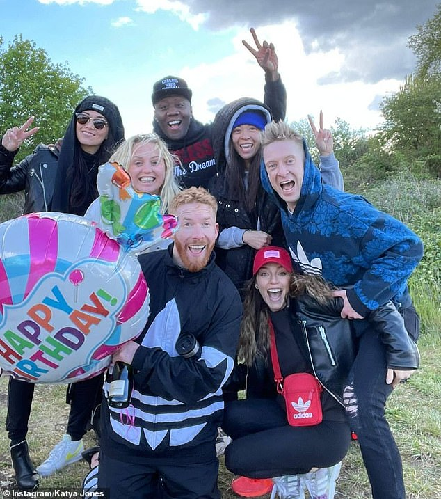 Big day:The first shot saw Neil smile for the camera with friends as held a giant balloon which read Happy Birthday