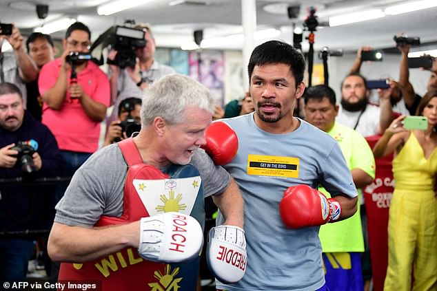 His long-time trainer Freddie Roach (pictured left with Pacquiao) said he'll have one or two more fights before running for president in 2022