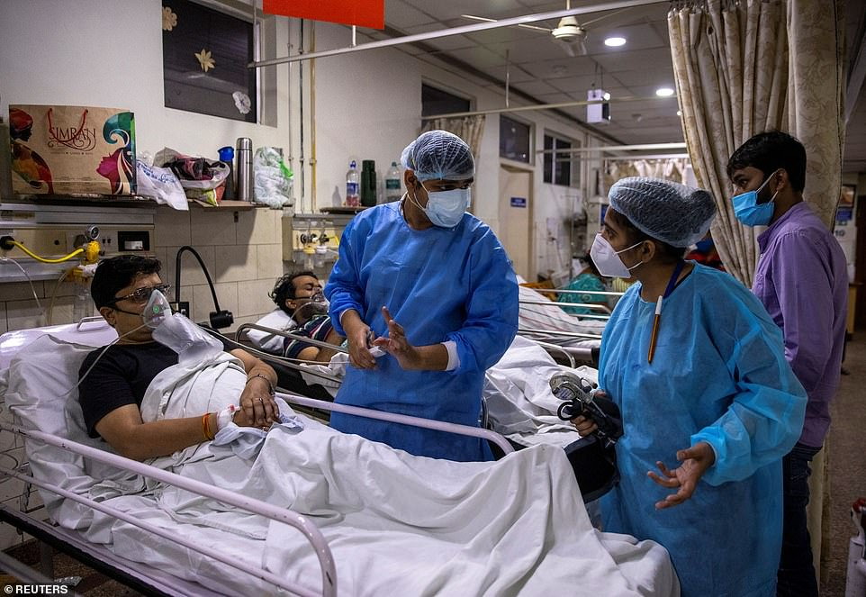 Rohan Aggarwal, 26, a resident doctor treating patients suffering from Covid, talks to staff during a mammoth 27-hour shift at a hospital in New Delhi