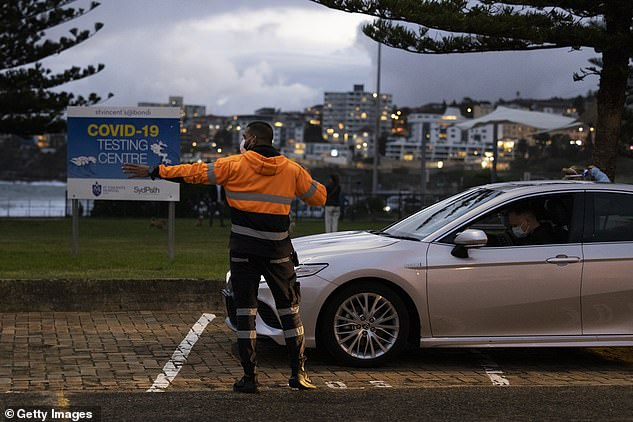 Pictured: Security staff direct traffic as people arrive at the Bondi Covid-19 testing clinic on May 5 - hours after the shock new case was announced