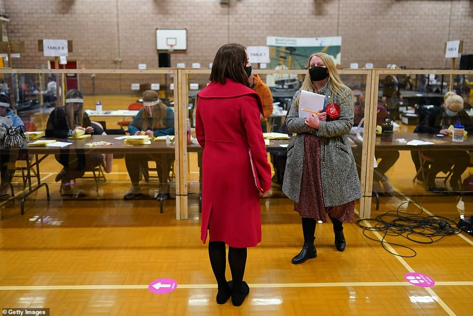 The seat has been held by Labour since its inception in the 1970s but the Conservatives believe they could win it with a majority of several thousand. Party observers look on as ballot papers are counted at the Mill House Leisure Centre