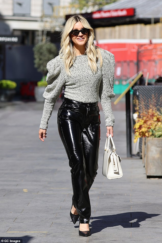 Elegant:She toted a white structured handbag with gold hardware while adding further glam with her cat-eye sunglasses with a black frame