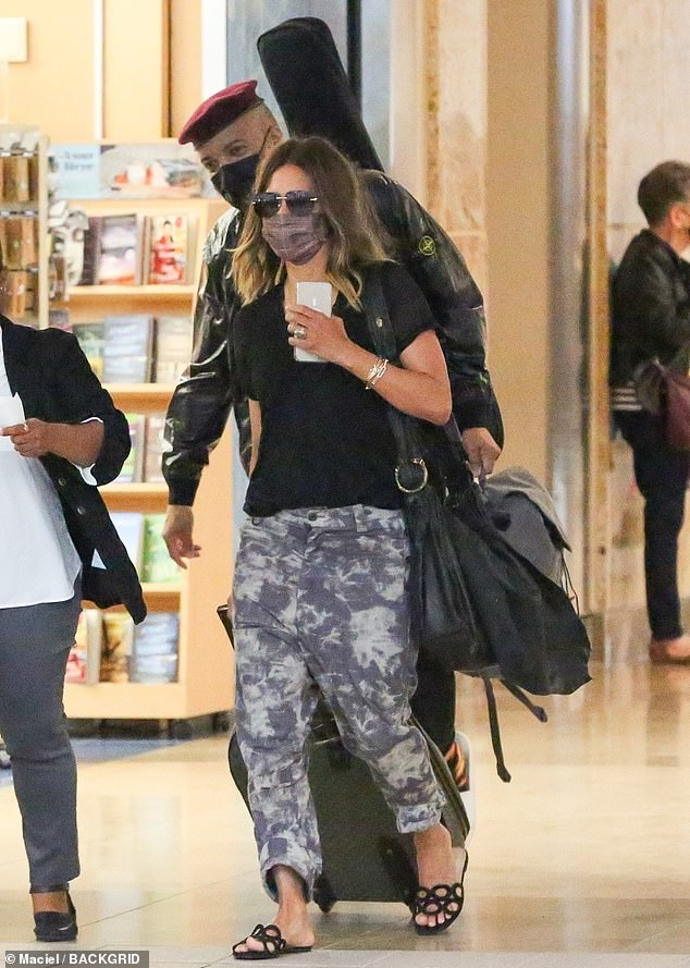 En route: Halle Berry and her boyfriend Van Hunt were seen heading for departures at an airport in Orlando, Fla. On Friday morning.