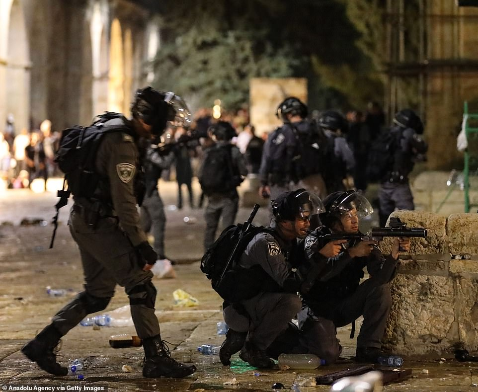 Israeli police duck behind a wall for cover as they tackled the mounting tensions
