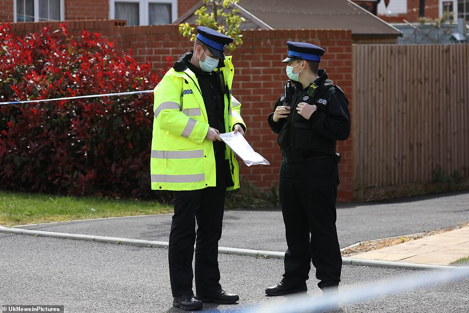 Masked police officers talk outside the house being searched by forensic officers. It comes after they arrested a suspect in the case