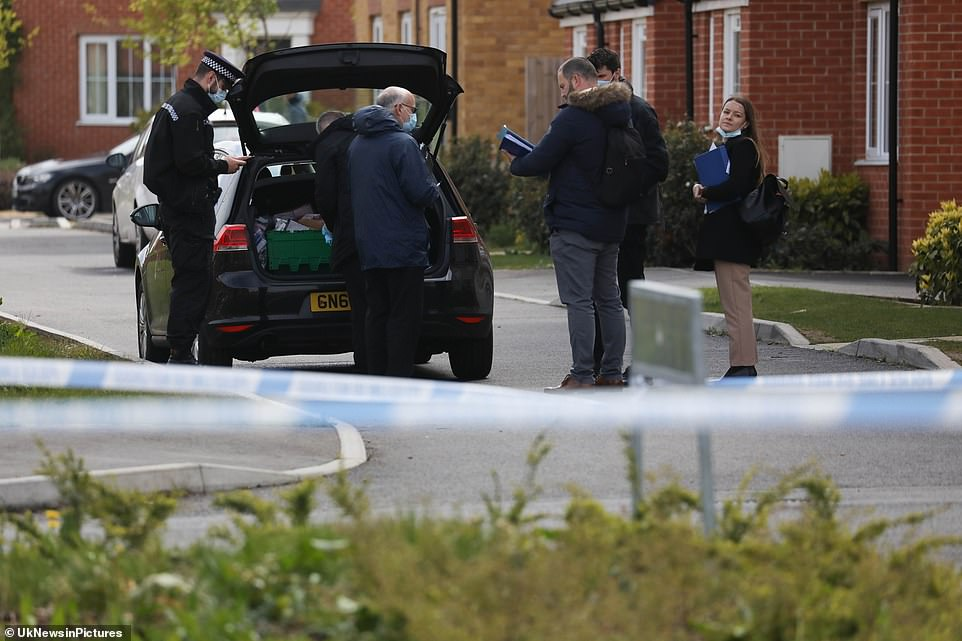 Police officers from Kent Constabulary are pictured holding clipboards as they stand outside the house being searched