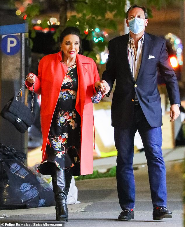 Holding hands: Dame Joan Collins, 87, looked stunning as she was blown away in an elegant floral-print dress while on a date with husband Percy Gibson, 56, in New York City on Saturday night.