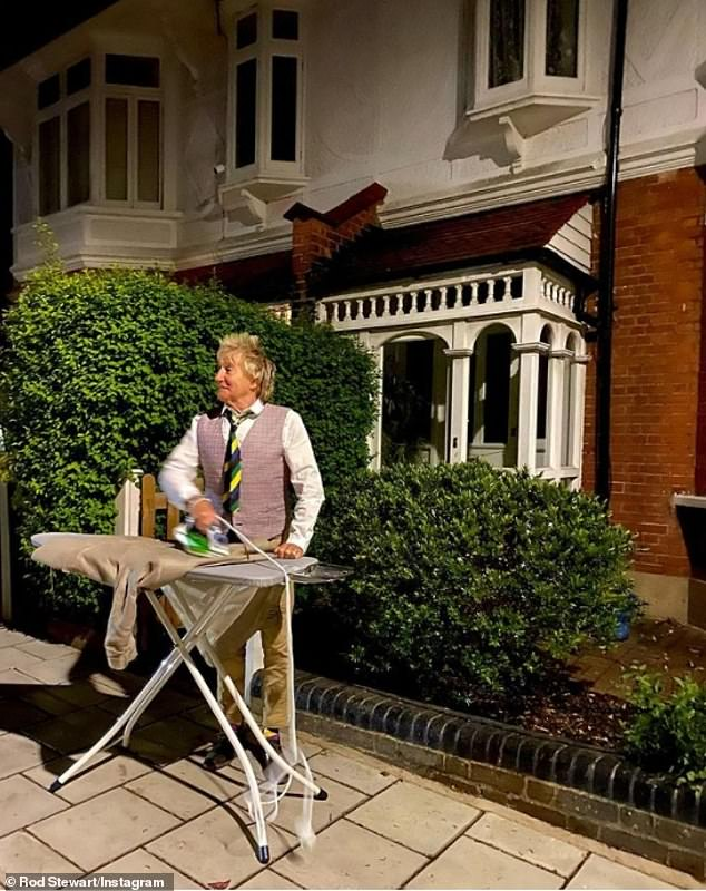 'Ironing out the crease of life': Rod Stewart posed in a waistcoat and brightly coloured striped tie on Saturday night as he stood out on the street ironing a brown shirt