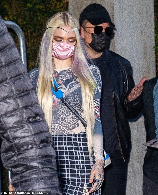 Notable: Distinctive band kept her center hair in place as she partied with soberly dressed Musk