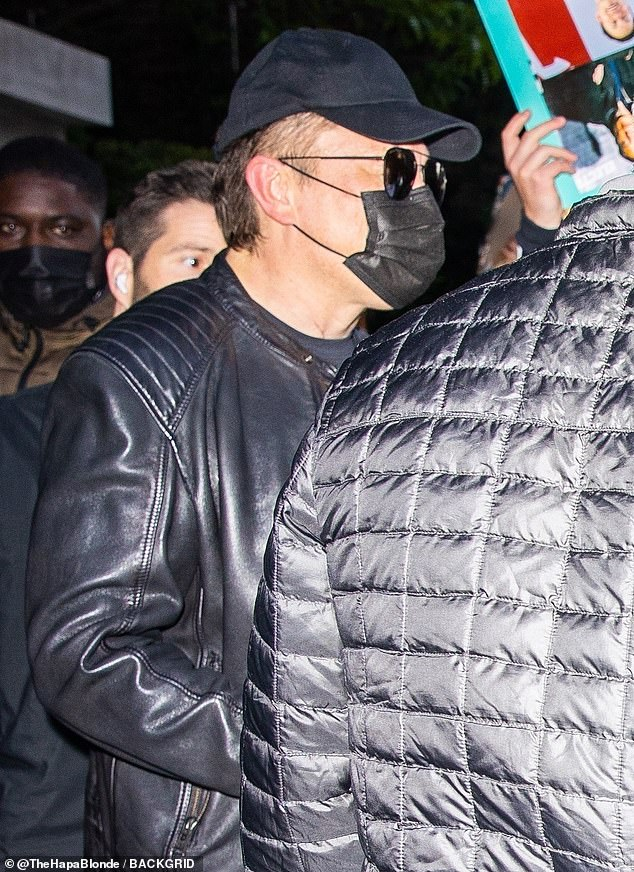 You're Surrounded: Musk was accompanied by an assortment of fans and bodyguards as he stepped out after his Saturday night live entertainment concert