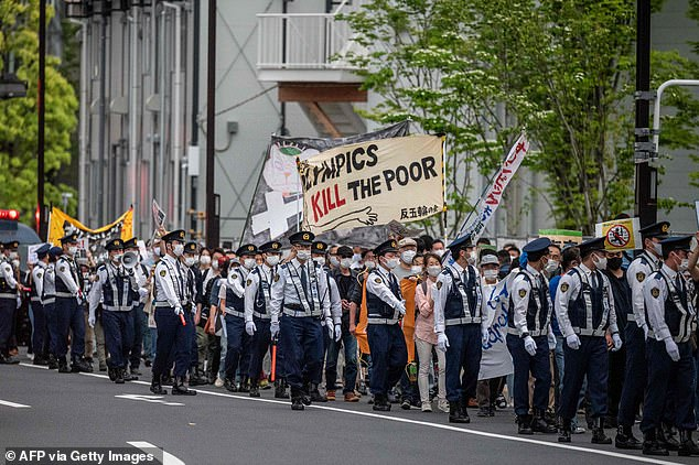 Locals marched, while monitored by police, holding banners reading 'Olympics kill the poor'