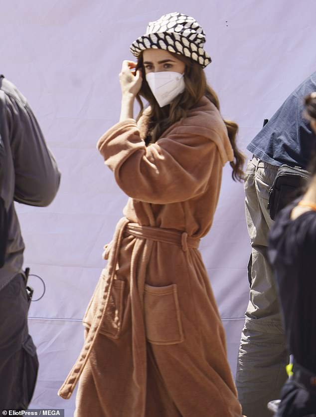 Covered: The actress then donned an elegant beige-colored dress as she walked across the set
