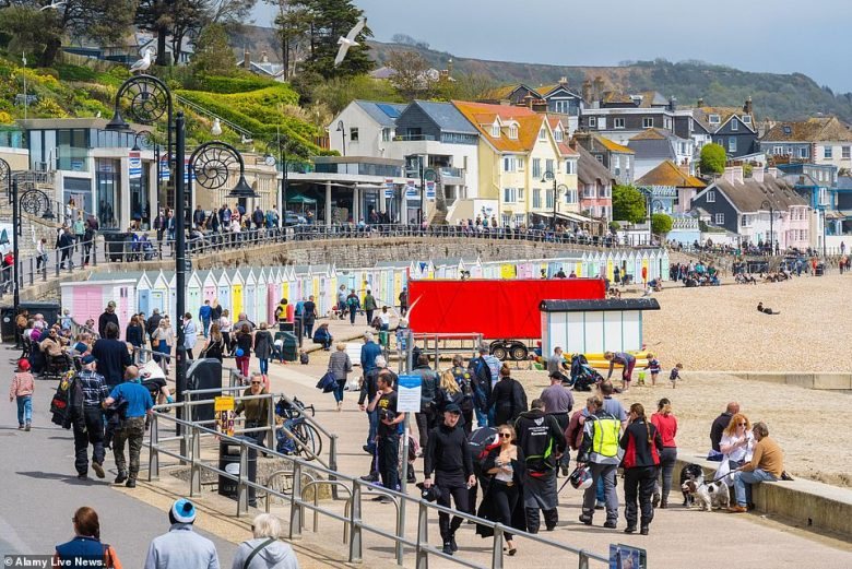 YESTERDAY: People enjoy the sunshine in the resort of Lyme Regis in Dorset yesterday as the UK welcomed warmer weather
