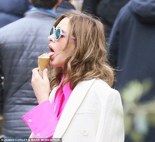Stylish: Wearing a fuchsia shirt under a slung camel white coat, Trinny kept the sun at bay with a trendy pair of mirrored sunglasses
