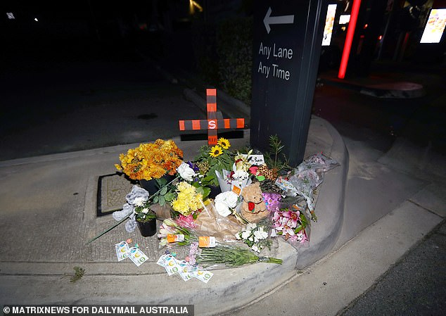 Locals set up a small memorial complete with flowers, handwritten notes, teddy bears and lollipops attached to the Kids Helpline number for others to take