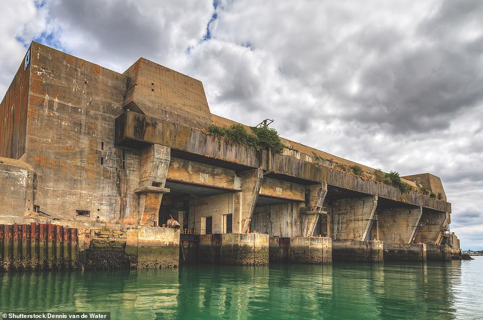 """LORIENT SUBMARINE BASE, LORIENT, FRANCE: With the fall of France to the Germans in mid-1940, the Kriegsmarine set about establishing protected Atlantic bases for its U-boat fleet. McNab writes: 'Here we see the formidable Keroman 3 (K3) U-boat pen at Lorient. With wet cells for housing seven U-boats, the K3 pen was virtually impregnable to conventional bombing, courtesy of a roof 7.6m (25ft) thick, including a one-metre (three-foot) air gap in the middle to disperse explosive force. On August 6, 1944, an RAF bombing raid hit the bunker with a 5,454kg (12,000lb) """"Tallboy"""" bomb, but the structure was not penetrated. Even today the complex of storage cells evoke a sense of physical defiance'"""