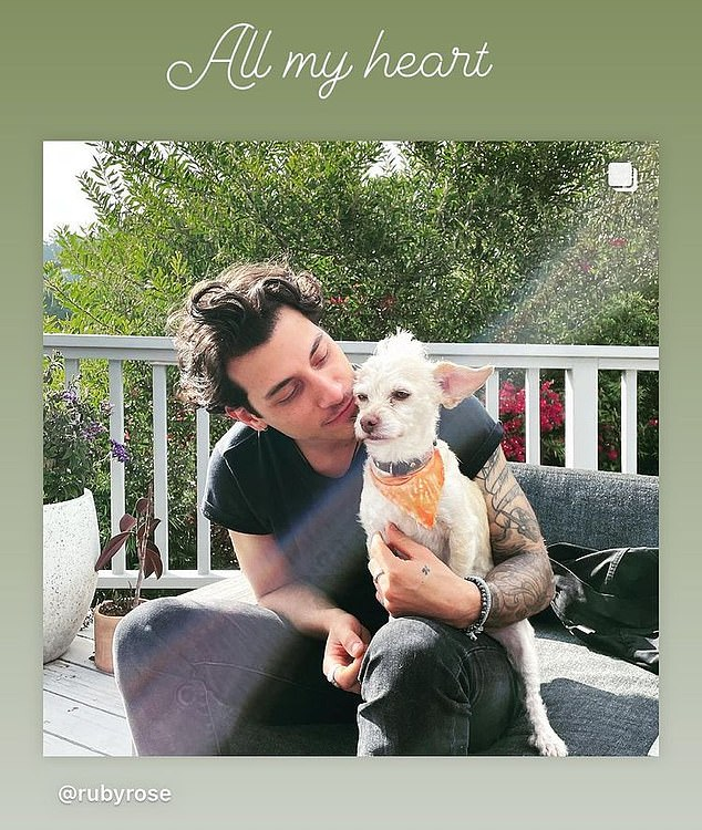 Hmm: Ruby also uploaded an Instagram Story photo of Rob cuddling a dog, alongside the caption: 'All my heart'