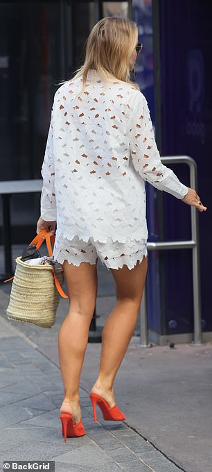Foot candy:She injected a pop of colour with orange open-toe mules which complemented the tangerine handles on her straw handbag