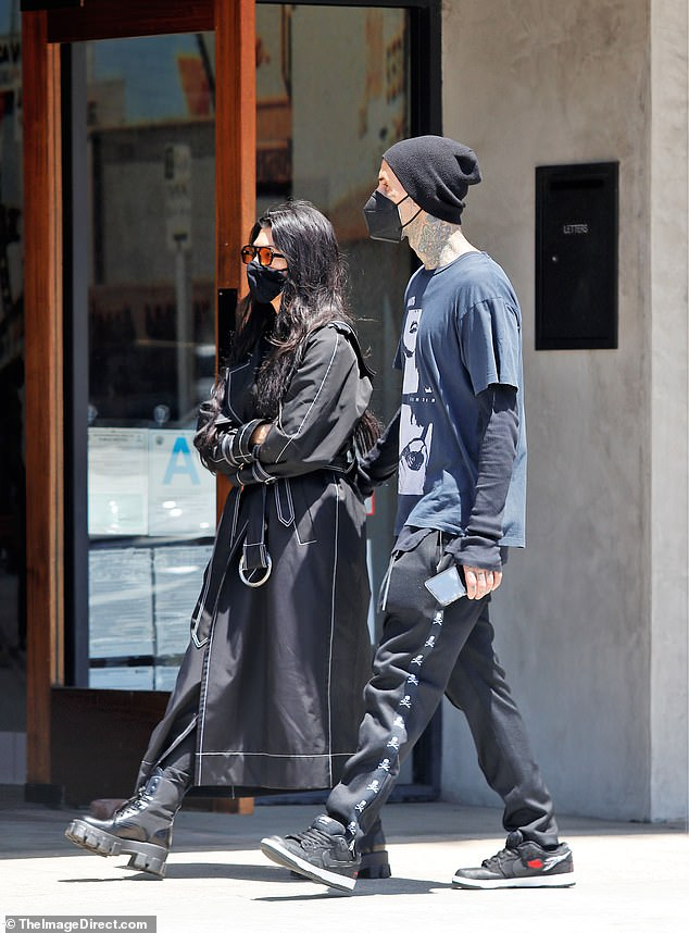 Change of pace: Kourtney Kardashian appeared to be in tune with her drummer beau as she stepped out wearing a trench coat and combat boots in Los Angeles on Tuesday