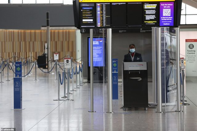 A BA member of staff wearing a face mask stands next to a coronavirus testing centre in Terminal 5 in Heathrow