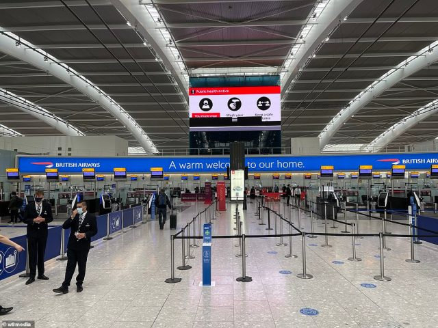 A shot of Terminal 5 in Heathrow shows social distancing markers and public health messaging on 'hands, face and space'