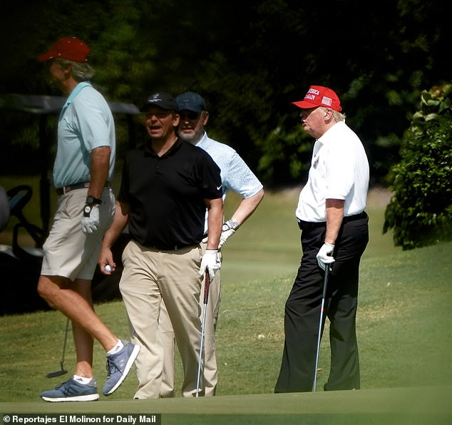 Donald Trump and Florida Gov. Ron DeSantis are close allies and friends - above DeSantis (in the black shirt) golfs with Trump at his Trump International Golf Club in West Palm Beach