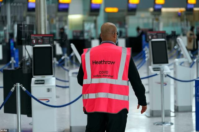 A Heathrow COVID safety marshal patrols the departures area in Terminal 5 at Heathrow Airport in west London today