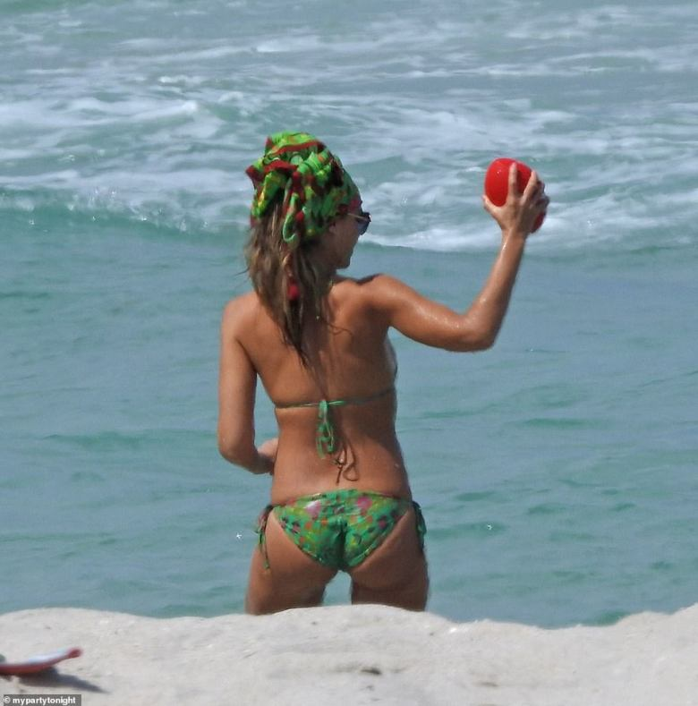 Beach babe: Alba took to the waves where she and husband tossed an orange football between the two of them