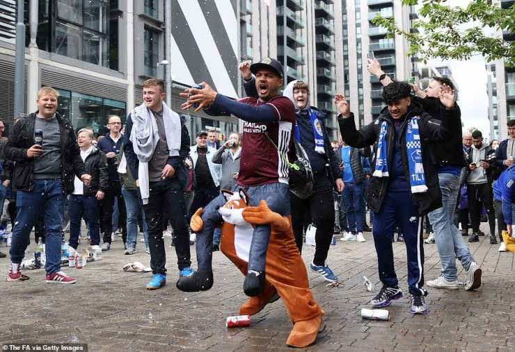 A Leicester fan wearing a fox outfit sings on Wembley Way as fans get in the mood ahead of the FA Cup final