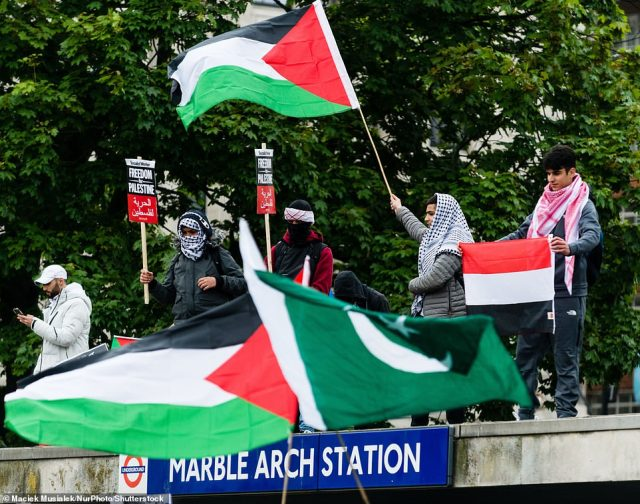 Protesters stood above the entrance to Marble Arch underground station near Hyde Park
