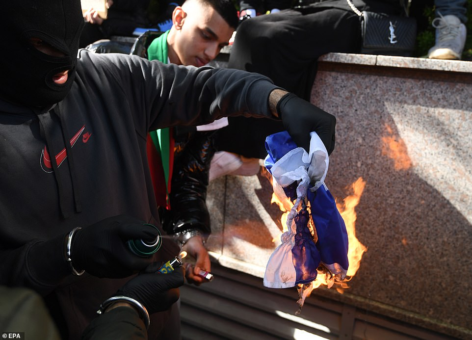 Pictured:Supporters of Palestine burn the Israeli flag during a demonstration outside the Israeli embassy in London, Britain, 15 May 2021