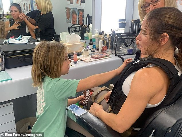 Family affair! One photo shows Elsa's son attempting to touch her faux bullet-proof vest as she sat in the makeup chair