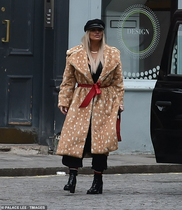 Wow: Kerry Katona, 40, turned heads in an oversized beige fur coat that was speckled with white spots alongside a trendy baker boy hat when she stepped out on Saturday