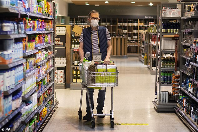 Retail giants have also been pushing for the one-meter-plus social distancing rule to be removed, as it reduces the number of shoppers able to enter stores at any one time.  Pictured: A shopper wearing a mask in an east London supermarket