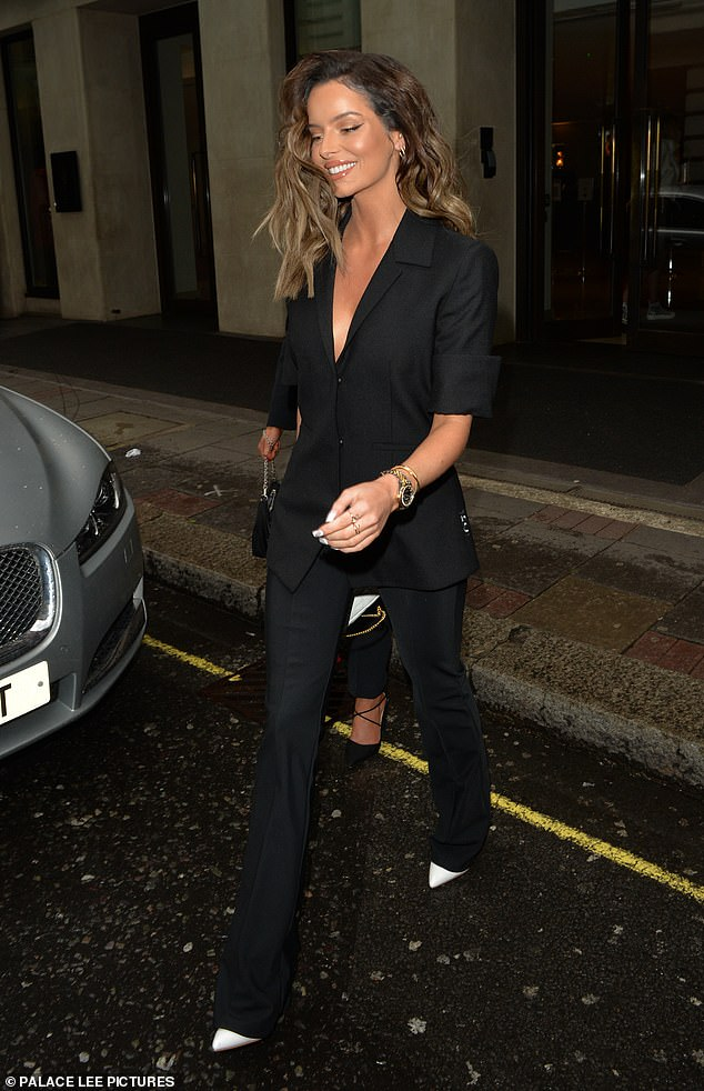 Chic: Maura, 30, wore a matching black pantsuit for the outing with a plunging neckline that showcased her cleavage