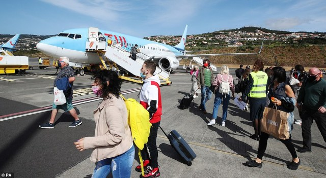 Passengers disembark from an early morning flight to Madeira, one of the government's green list destinations on Monday