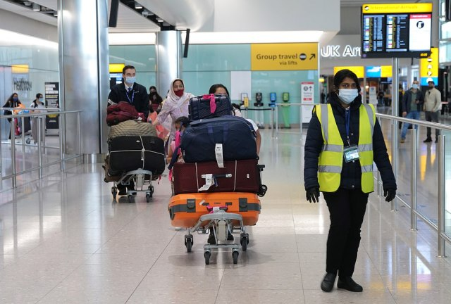 Passengers push their luggage as they walk through the arrivals hall at London Heathrow Airport's Terminal 2yesterday