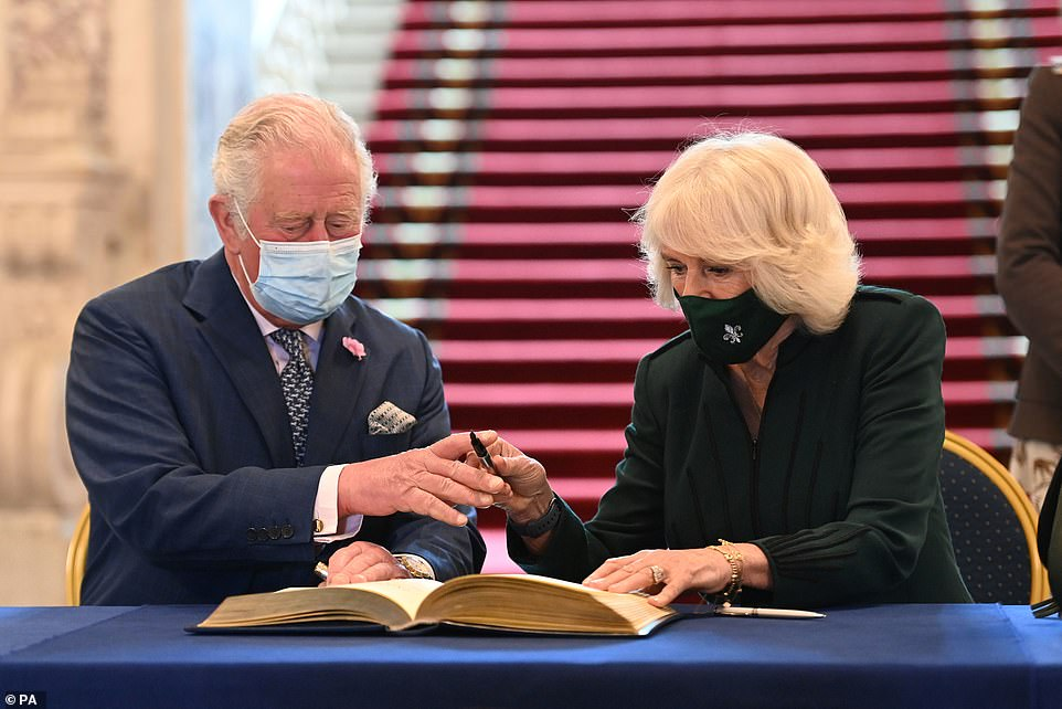 The Prince of Wales and the Duchess of Cornwall are seen signing the visitor's book during a visit to Belfast City Hall