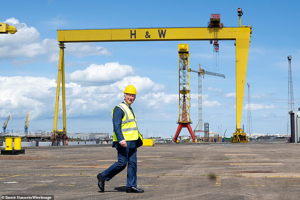 Prince Charles is seen at the Harland & Wolff shipyard beneath Samson and Goliath - the twin shipbuilding gantry cranes - in the same spot as his late father Prince Philip