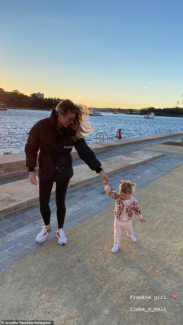 Good times: Jennifer Hawkins and husband Jake Wall took their one-year-old daughter Frankie for a walk on Tuesday near a dock