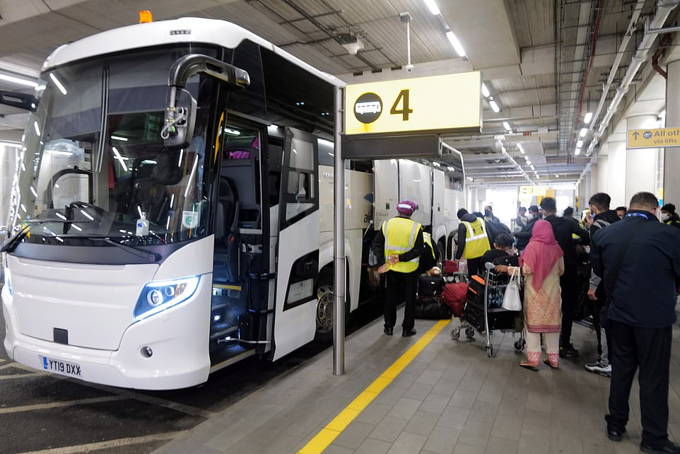 Passengers wait to board a coach to a quarantine hotel outside Terminal 2 at Heathrow Airport