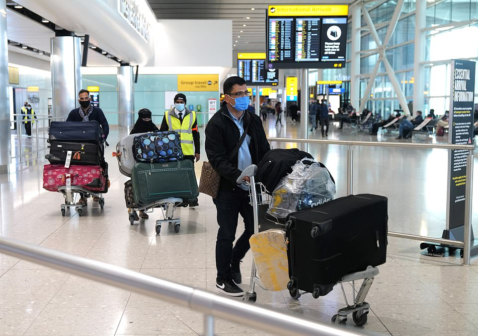 Passengers walk through the arrivals hall at London Heathrow Airport's Terminal 2 yesterday